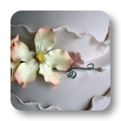 Shimmering Ivory Wedding Cake with Asymmetrical Ruffles.